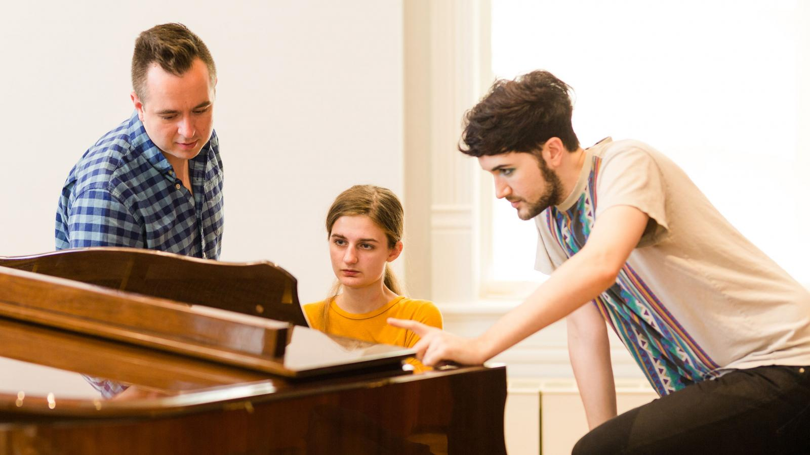 female student sits at piano with two men looking at sheet music with her
