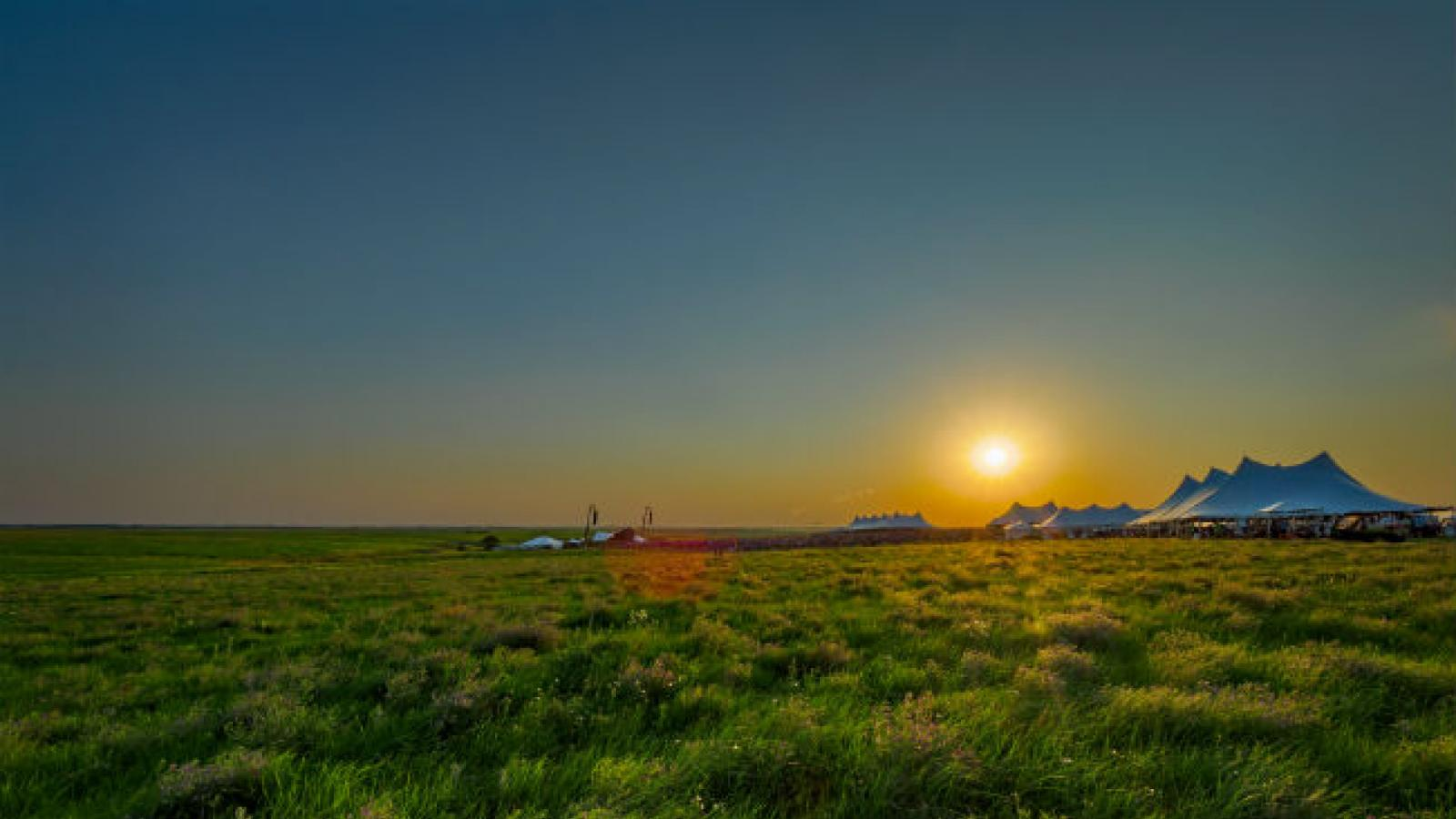 White tents at sunsets in middle of Kansas grassland prairie