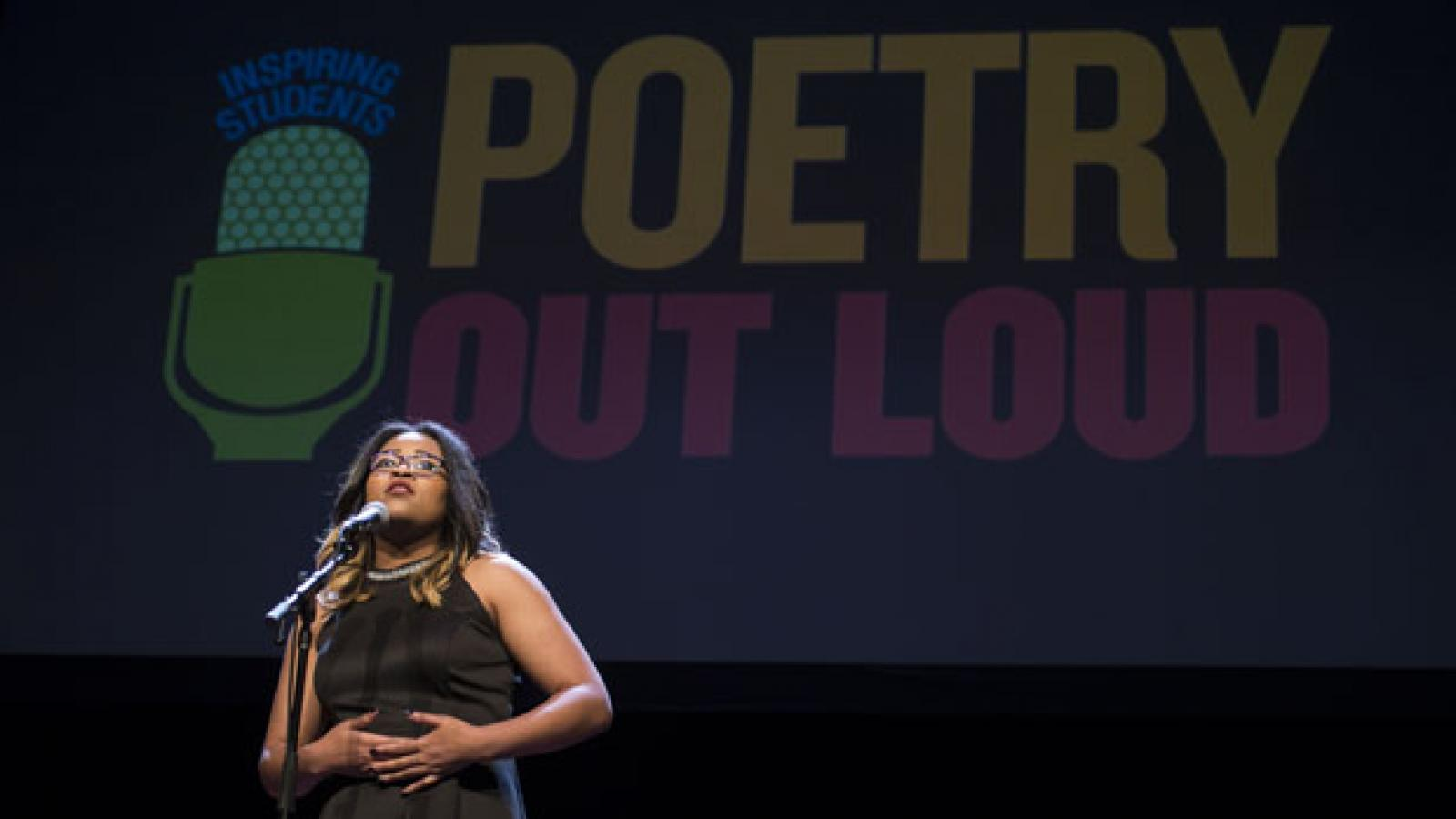 A teenage girl in a black dress speaks at a microphone with a Poetry Out Loud sign behind her.