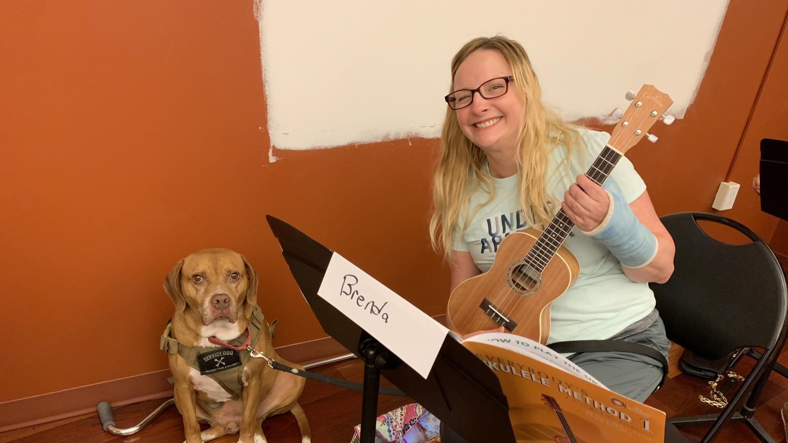 Woman with ukelele sitting and smiling with service dog sitting next to her.