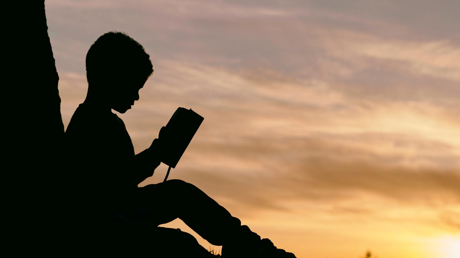 Silhouette of young boy reading a book against the sunset