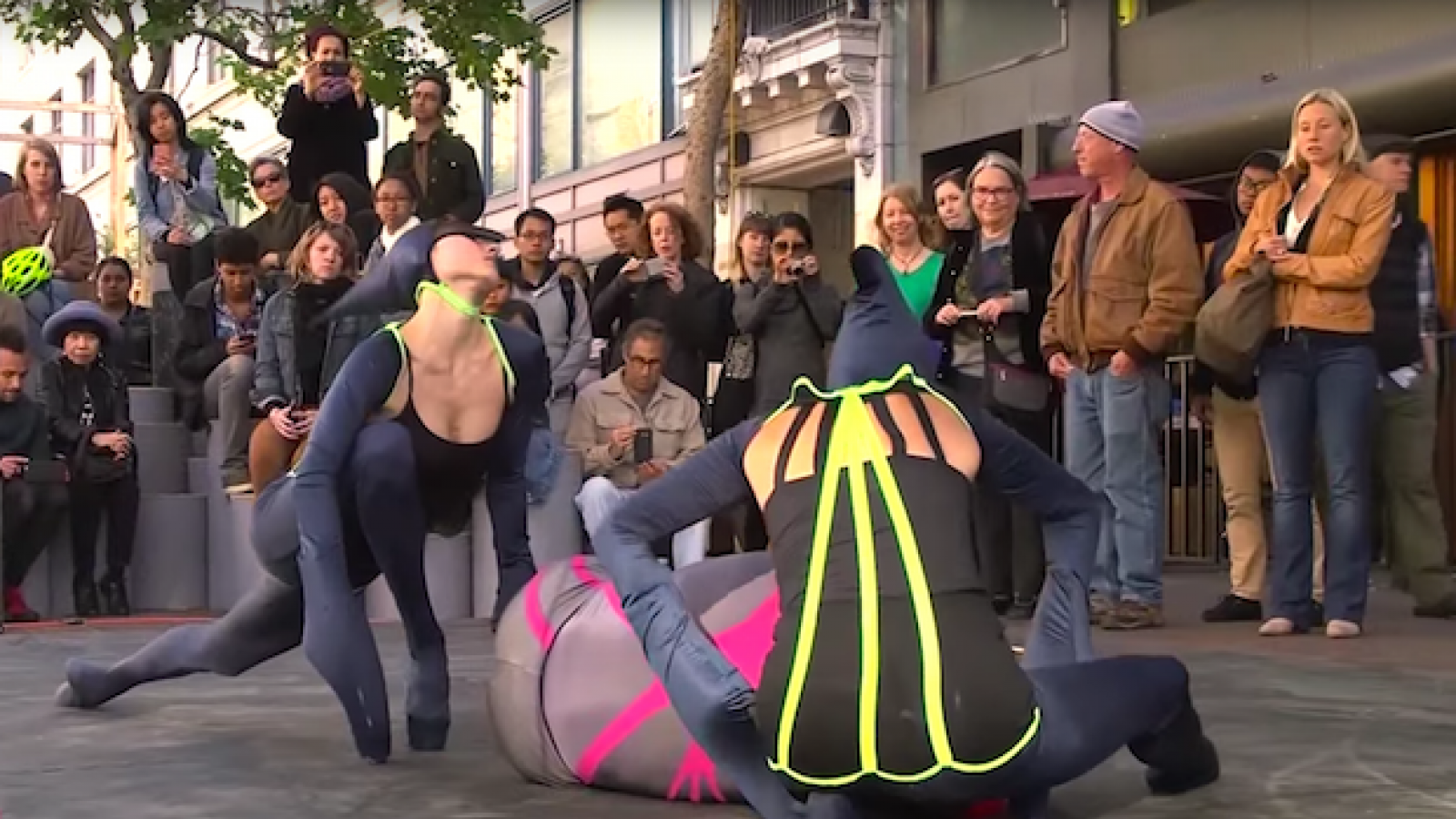 Dancers dressed as bugs dance on a city sidewalk for a crowd.