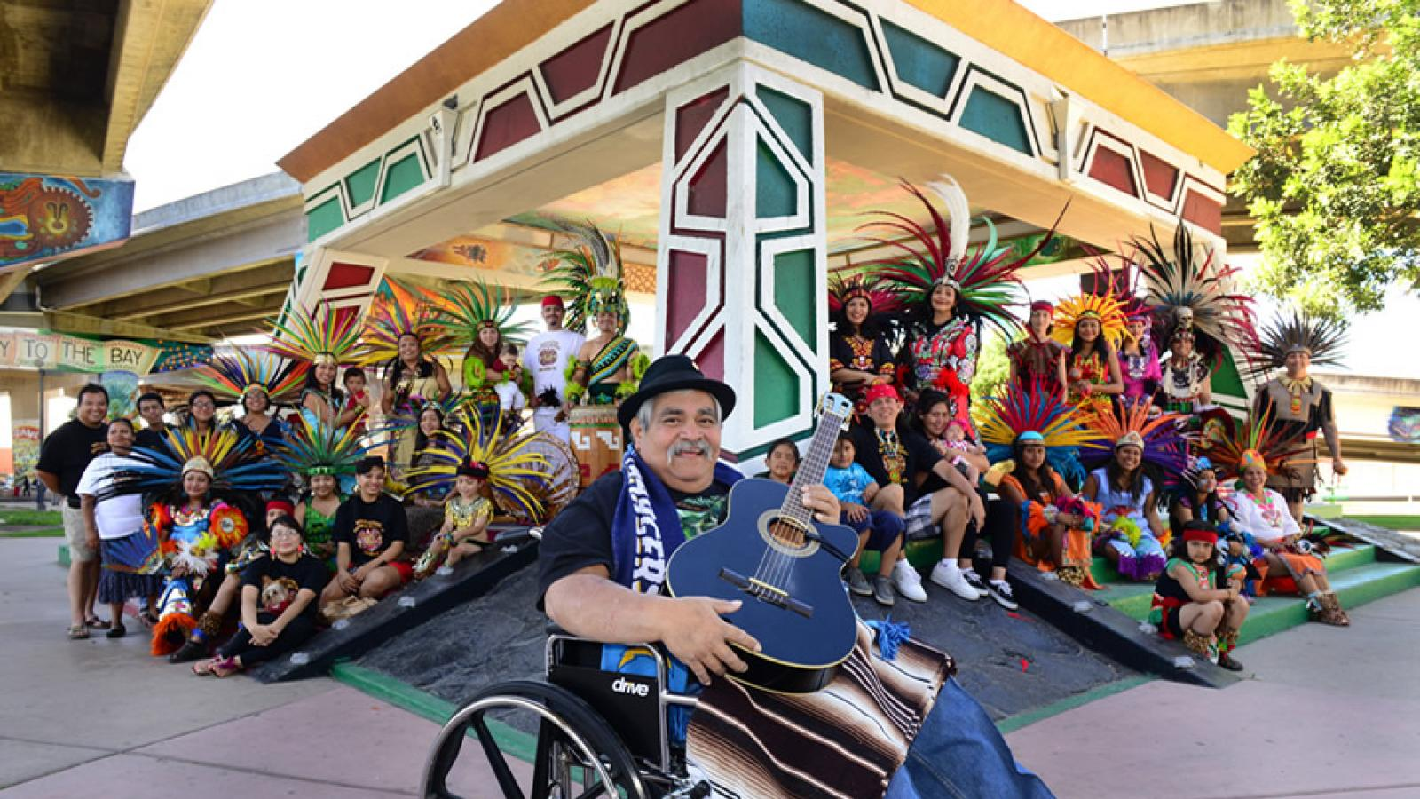 "Ramón ""Chunky"" Sánchez sits in a wheelchair, holding a guitar and smiling, in front of a large group of communitiy members and performers wearing colorful and elaborate Aztec costumes."