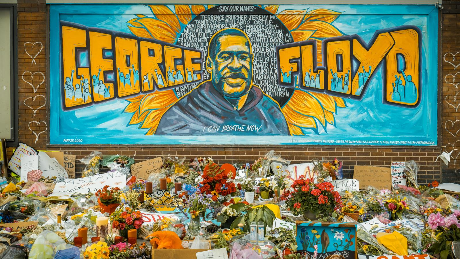 A painting of George Floyd on a building side with flowers in front of it.