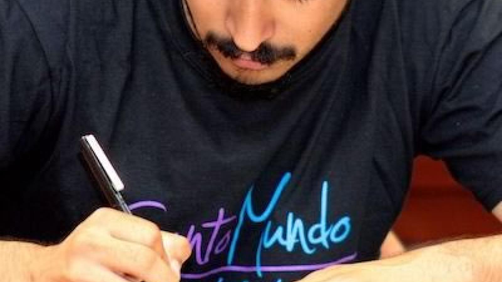 Headshot of a young Latino man wearing a hat and a Canto Mundo t-shirt bent over and writing on a page