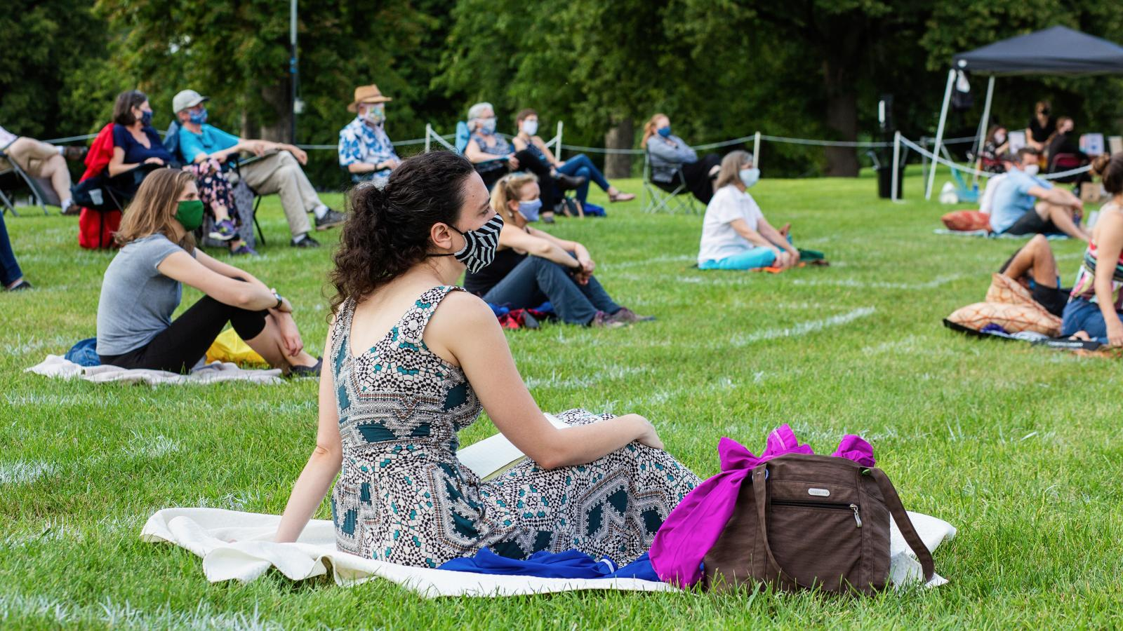 People wearing masks sit on picnic blankets on the grass while spread out from one another