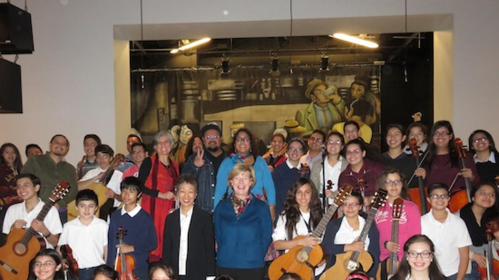 Jane Chu and Senator Tammy Baldwin with a large group of kids holding stringed instruments