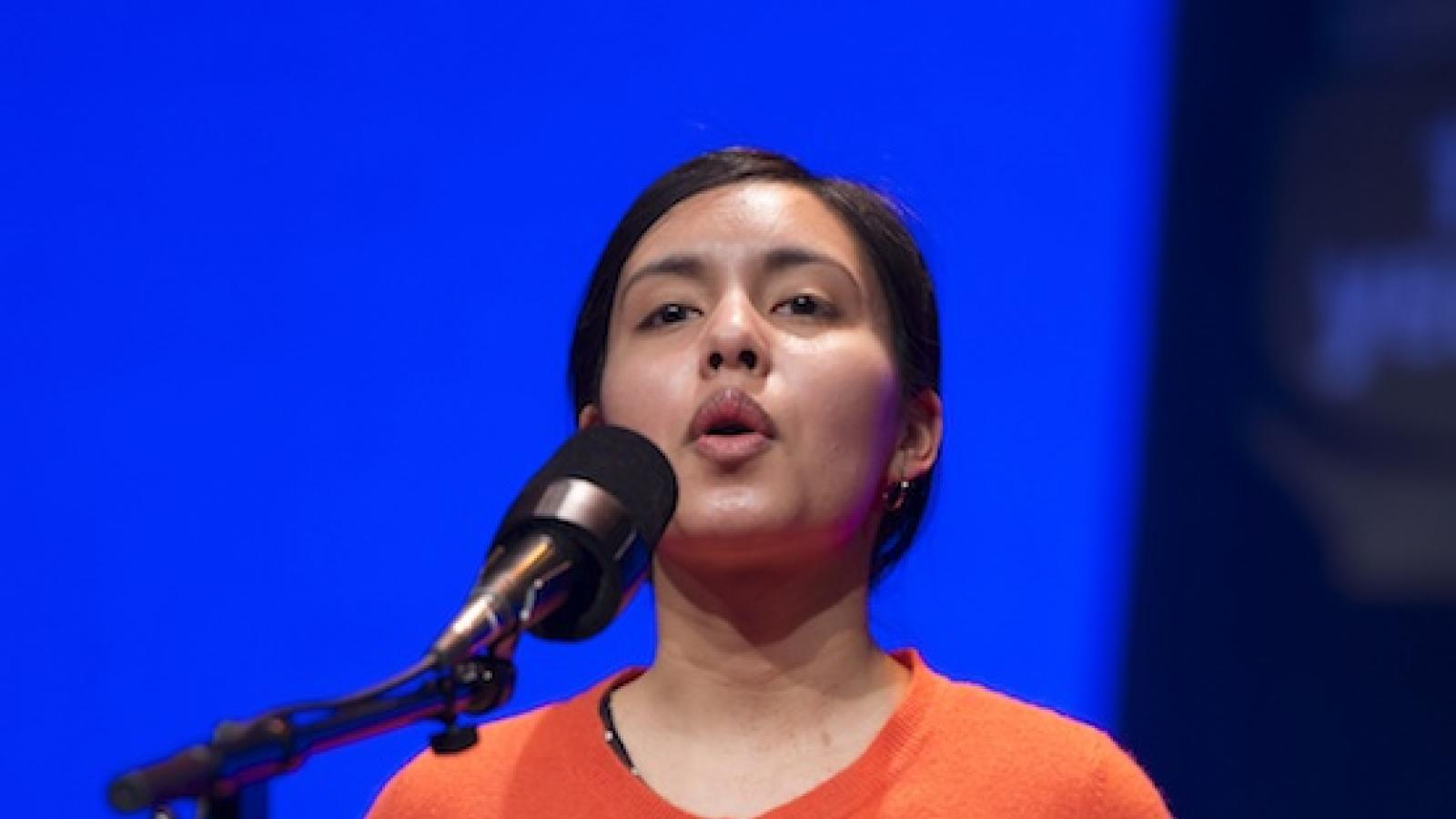 a young Hispanic woman wearing an unbuttoned orange sweater over a black dress with white polka dots recites into a microphone
