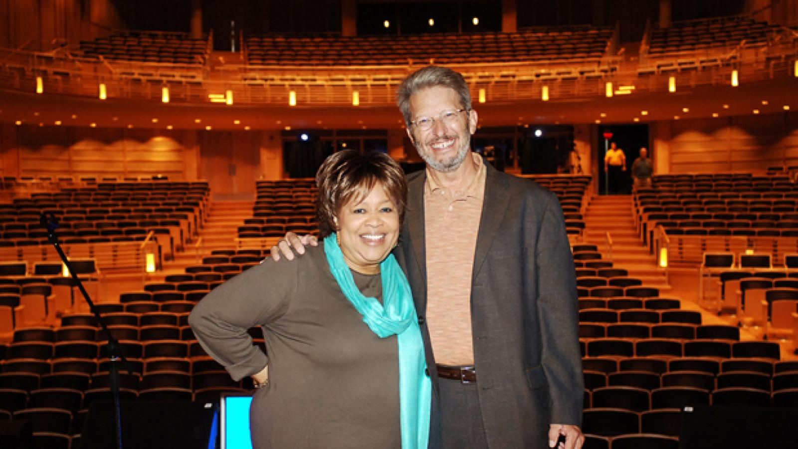a woman in a brown shirt and a blue scarf stands on a stage with a man with a beard wearing a brown suit.