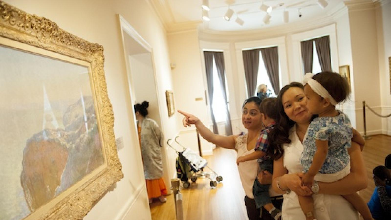 two women holding their toddlers and looking at a landscape painting on the wall of a museum