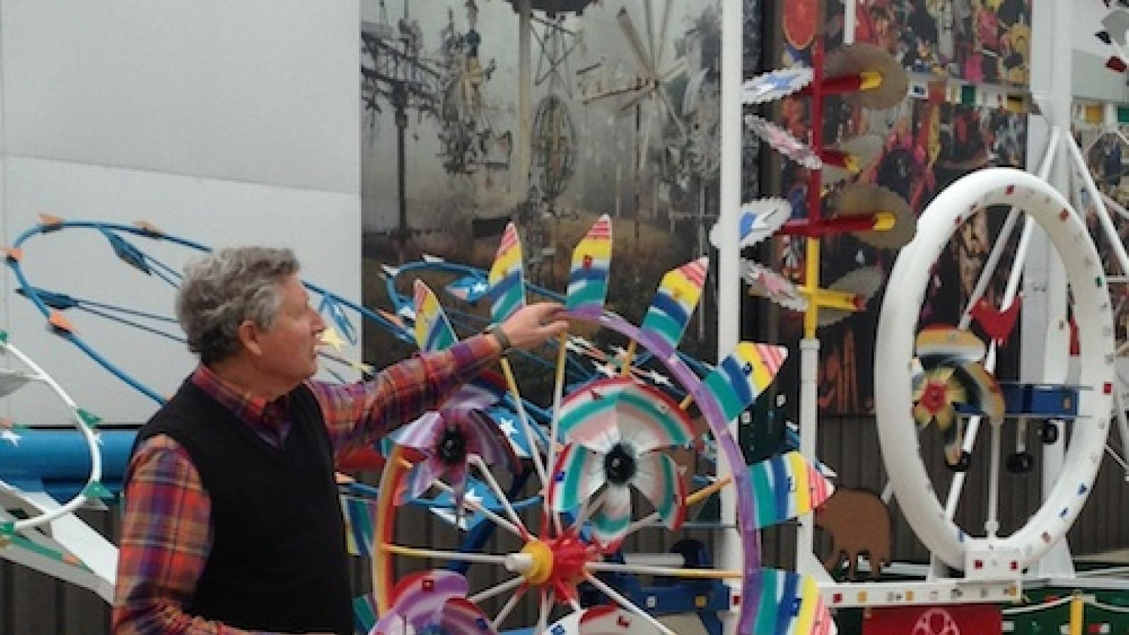 A man shows off a whirligig which is like a looks like a decorated spinning wheel