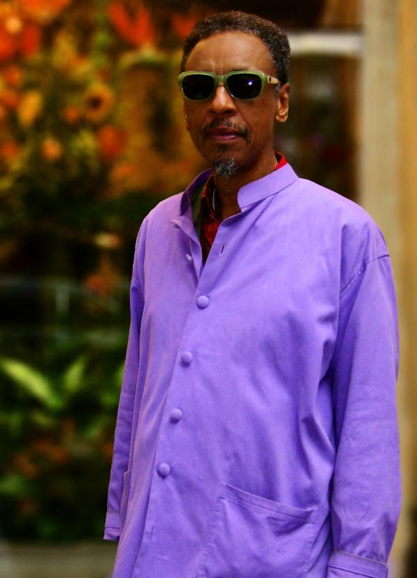 Portrait of man in purple shirt wearing sunglasses.