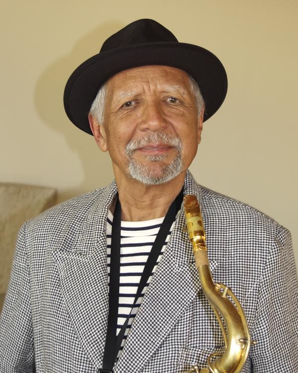 Man in hat holding saxophone.