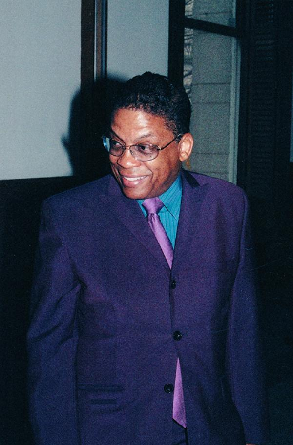 Man in purple suit, smiling.